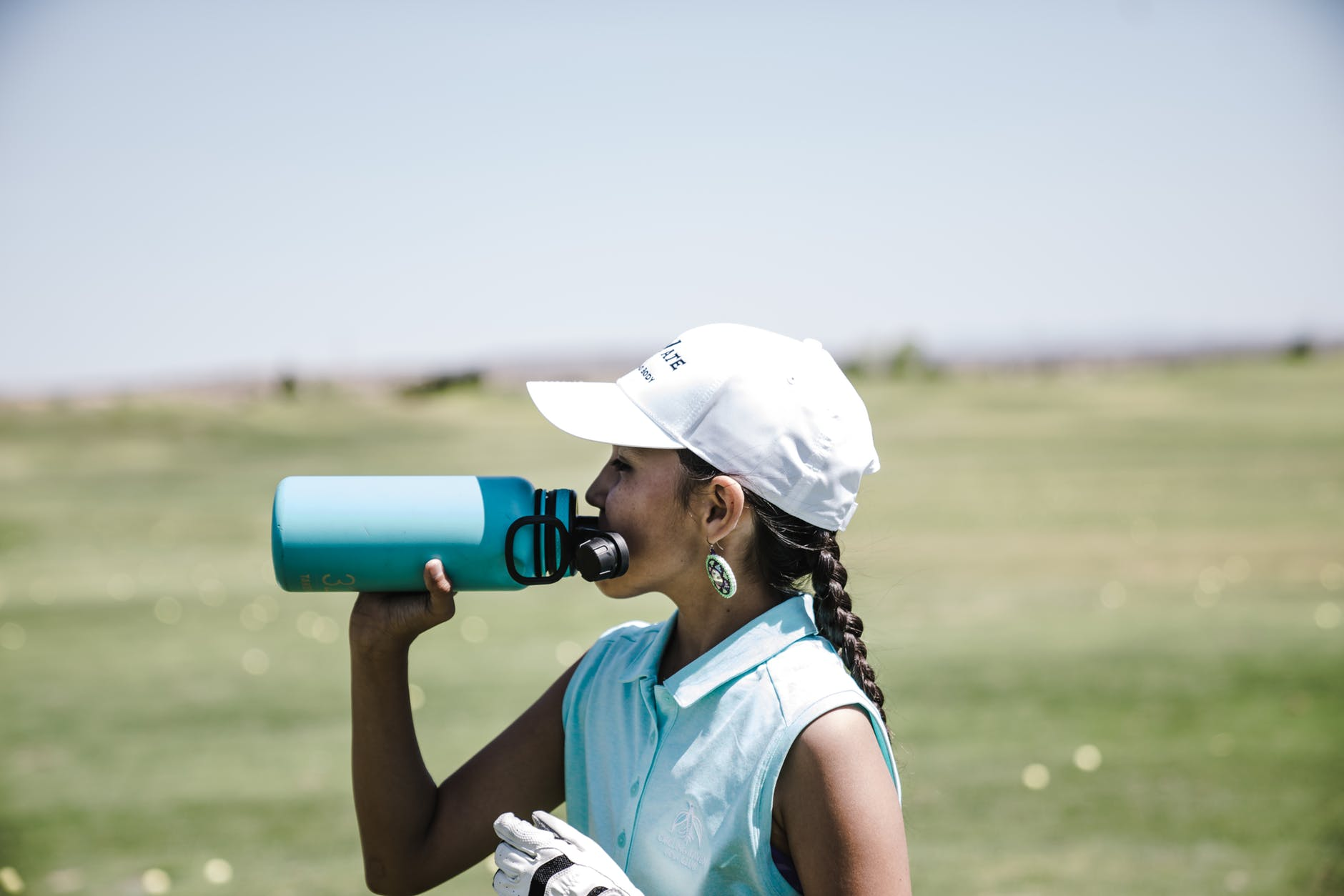 image of a golfer staying hydrated on the golf course